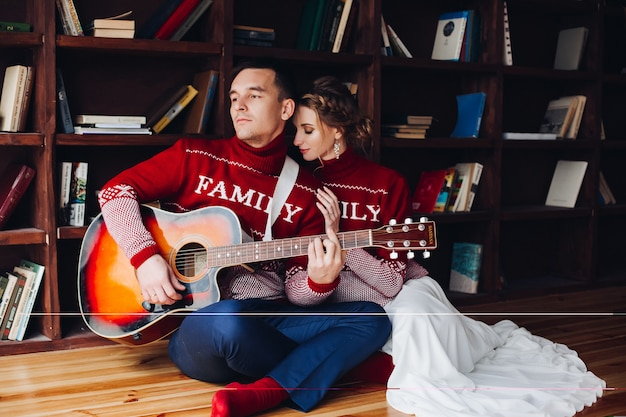 Пара играет на гитаре и обнимает Premium Фотографии