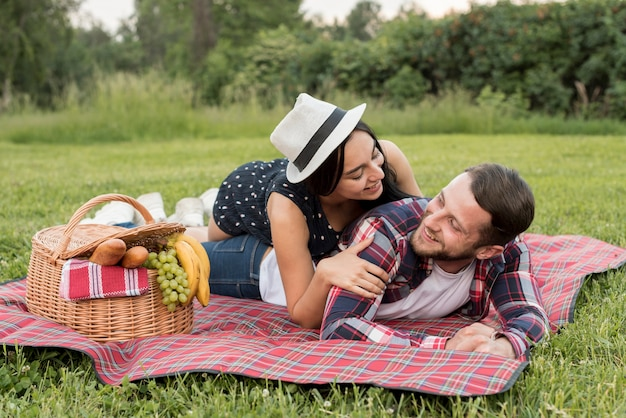 Couple playing on a picnic blanket Free Photo