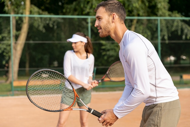 Couple playing tennis at duo Free Photo