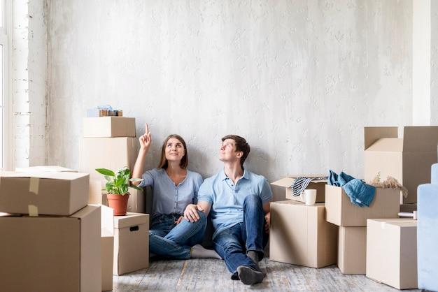 Пара, указывая вверх во время упаковки, чтобы переехать Premium Фотографии