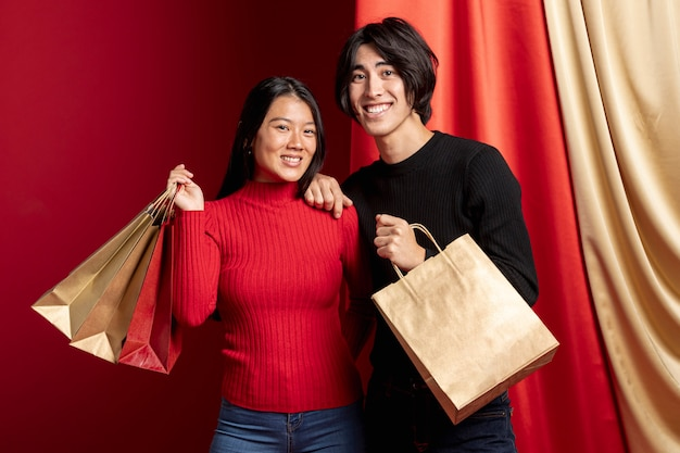 Couple posing and holding paper shopping bags for chinese new year Free Photo