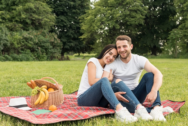 Couple posing on a picnic blanket Free Photo