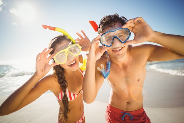 Couple posing with diving mask on beach Premium Photo