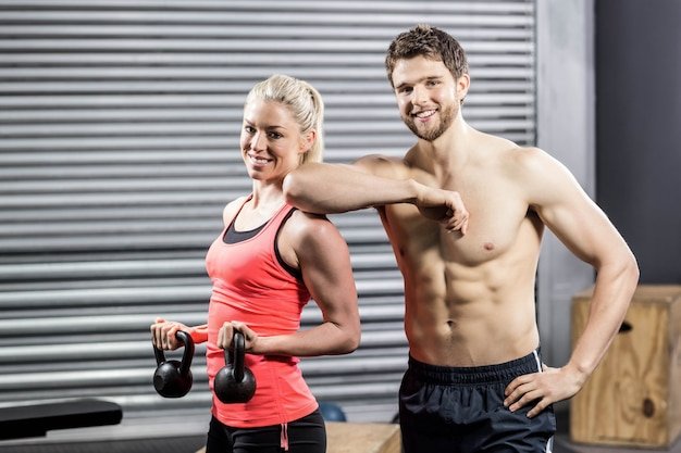 Couple posing with dumbbells at crossfit gym Premium Photo