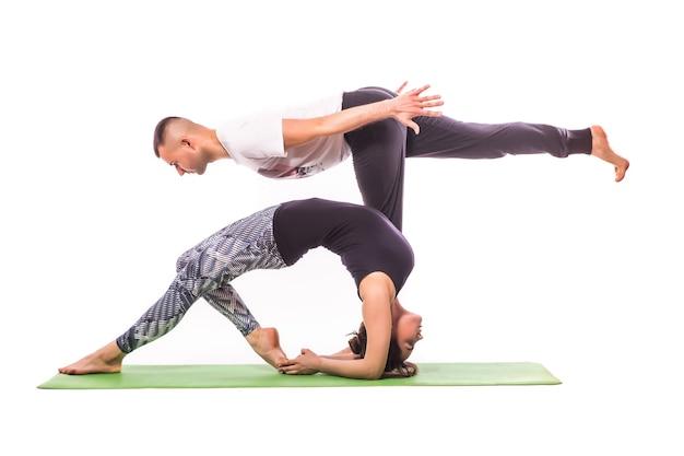 화이트 스튜디오에서 Acro 요가 연습하는 커플. 아크로 요가 개념. 쌍 요가. 요가 유연성 수업 운동 무료 사진