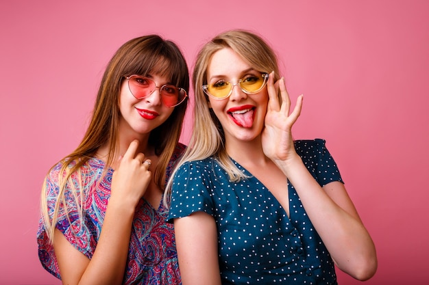 Couple of pretty best friends sister girls having fun together, wearing elegant summer pretty trendy dresses and sunglasses, posing at pink wall, hugs and smiling, party atmosphere. Free Photo