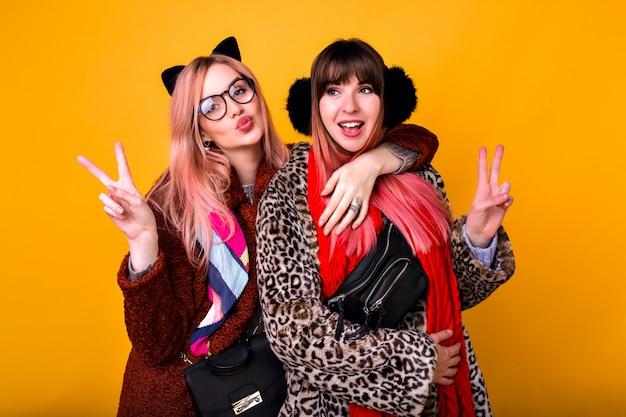 Coppia di ragazze sorelle dei migliori amici hipster piuttosto divertenti che fanno selfie al muro giallo, mostrando la lingua e sorridendo, indossando pellicce stampate primaverili alla moda, sciarpe, marsupio e occhiali trasparenti. Foto Gratuite