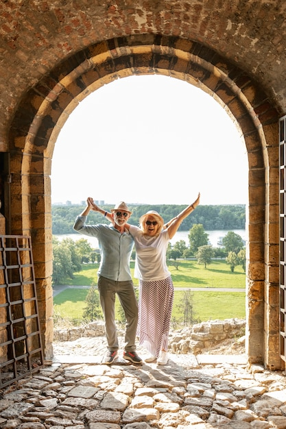 Couple raising their hands in the air in front of a door Free Photo
