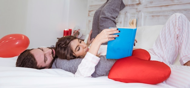Couple reading book lying on bed Free Photo