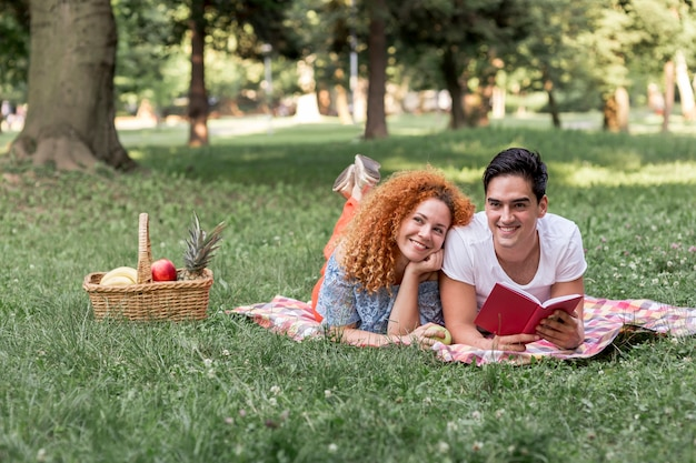 Couple reading a book together at the park Free Photo