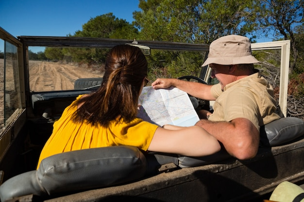Couple reading map while sitting in vehicle Free Photo