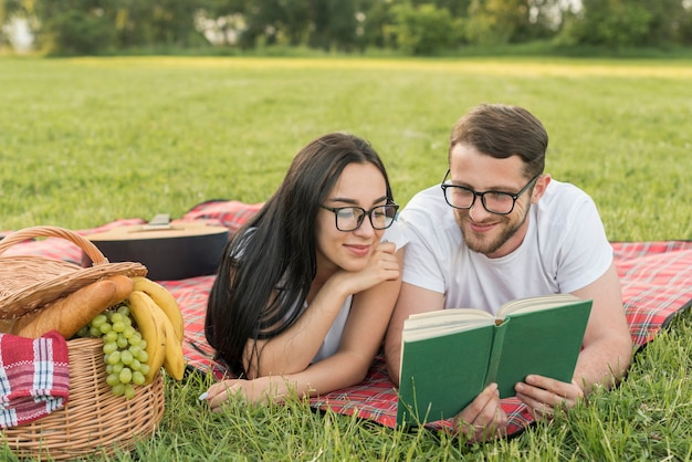 Couple reading on a picnic blanket Free Photo