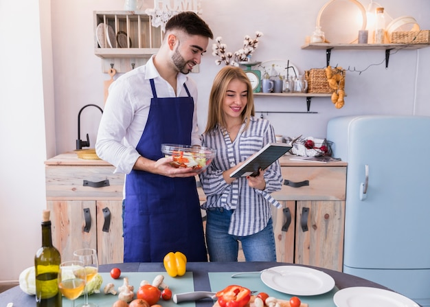 Couple reading recipe book in kitchen Free Photo