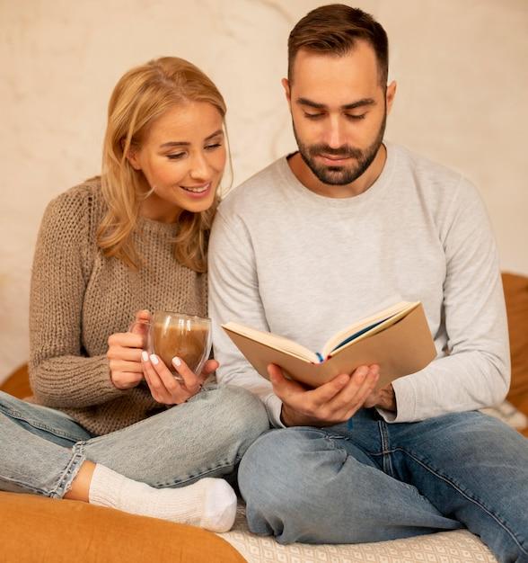 Пара, читающая вместе в помещении Premium Фотографии