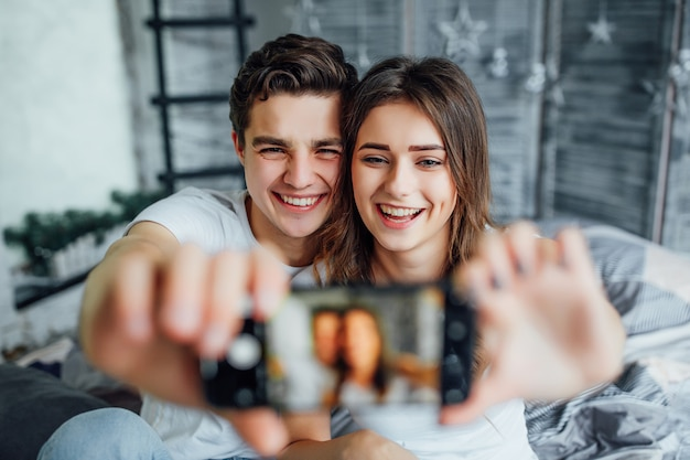 Couple relaxing in bed and taking a selfie Premium Photo