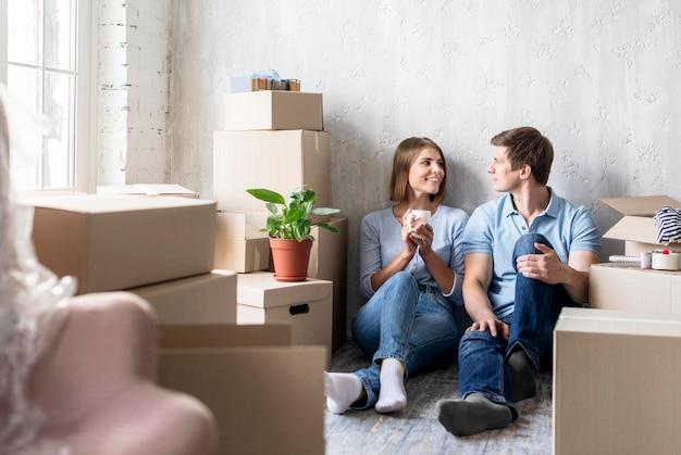 Пара расслабляется во время упаковки, чтобы переехать Premium Фотографии