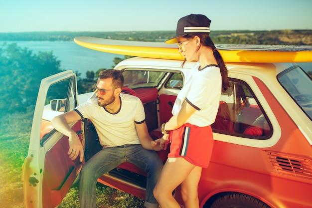 Coppia che riposa sulla spiaggia in una giornata estiva vicino al fiume Foto Gratuite