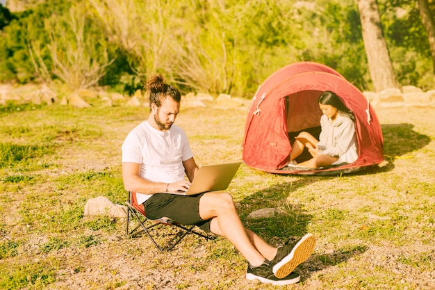 Couple resting in camping and working remotely Free Photo