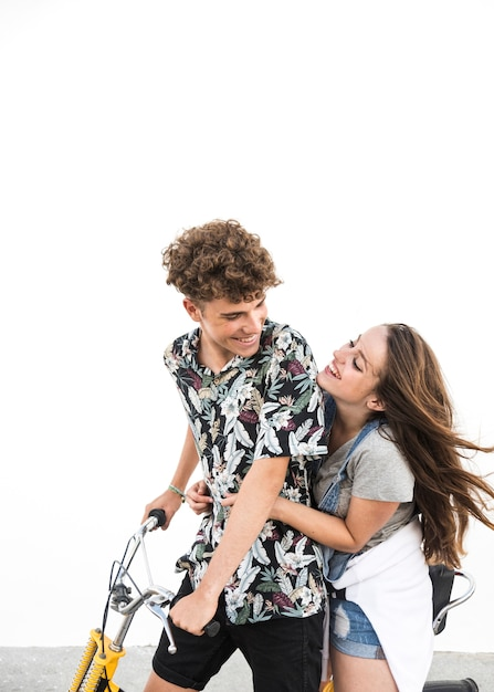 Couple riding bicycle looking at each other against white backdrop Free Photo