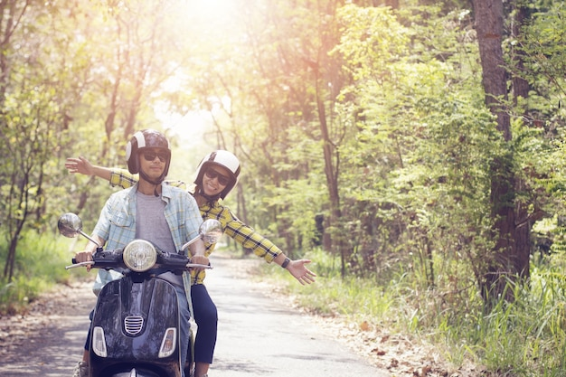 Couple riding their scooter through forest. life style idea concept Premium Photo