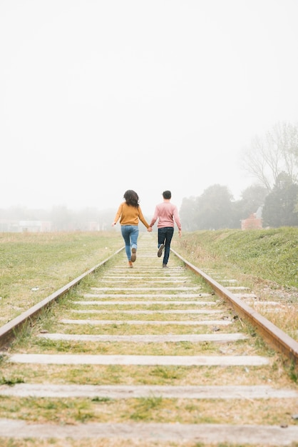 Couple running along railway and holding hands Free Photo