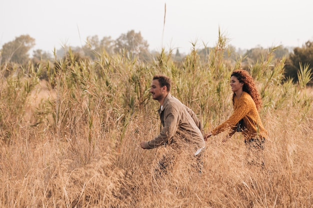 Couple running through wheat field Free Photo