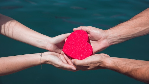 Couple's hand holding red heart shape against sea water background Free Photo