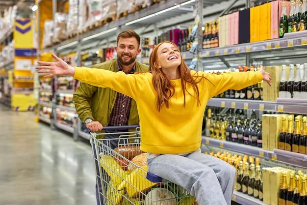 식료품 슈퍼마켓에서 함께 쇼핑하는 커플, 남자는 빨간 머리 여자 친구를 카트에 들고, 그들은 재미 있고, 시간을 즐기고, 여자는 행복하고, 팔을 벌립니다. 프리미엄 사진