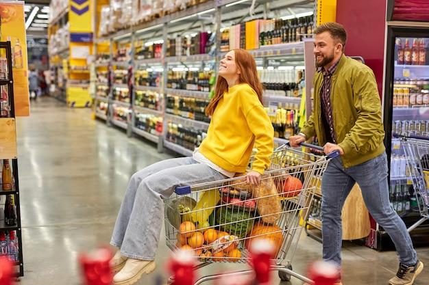 식료품 슈퍼마켓에서 함께 쇼핑하는 커플, 남자는 카트에 그의 빨간 머리 여자 친구를 운반하고, 그들은 재미 있고, 시간을 즐길 수 있습니다. 프리미엄 사진
