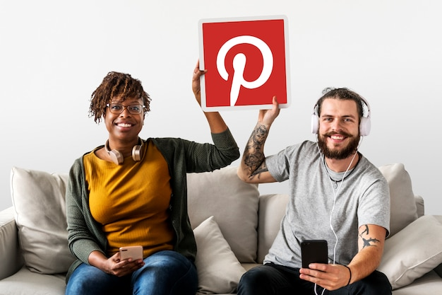 Couple showing a pinterest icon Free Photo