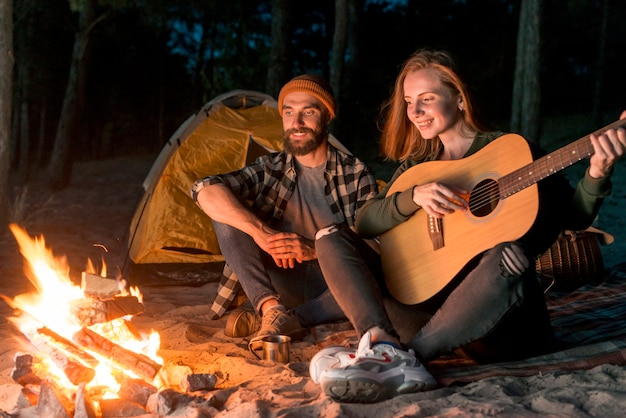 Couple singing by a tent with a campfire Free Photo