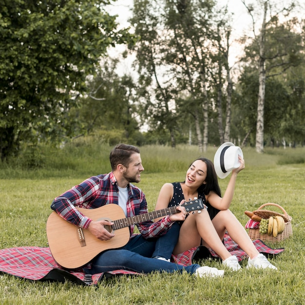 Couple singing on a picnic blanket Free Photo