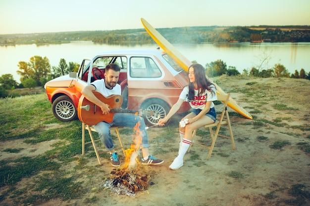 川の近くの夏の日にギターを弾いてビーチに座って休んでいるカップル 無料写真