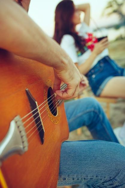 Пара сидит и отдыхает на пляже, играя на гитаре в летний день у реки Бесплатные Фотографии