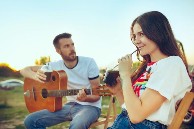川の近くの夏の日にギターを弾いてビーチに座って休んでいるカップル。愛、幸せな家族、休暇、旅行、夏のコンセプト。白人の男性と女性 無料写真