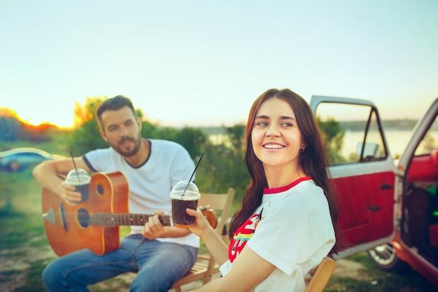 Пара сидит и отдыхает на пляже, играя на гитаре в летний день возле реки. любовь, счастливая семья, отдых, путешествия, летняя концепция. Бесплатные Фотографии