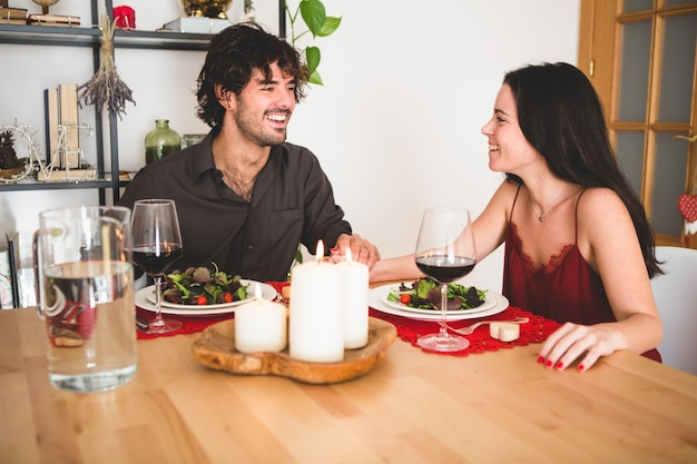Couple sitting at a table to eat smiling Free Photo