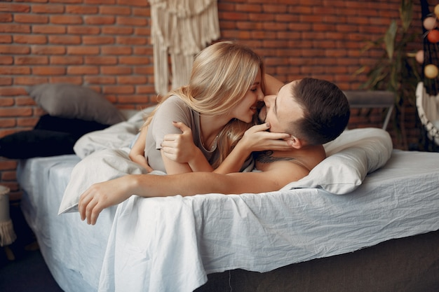 Couple sitting on a bed in a room Free Photo