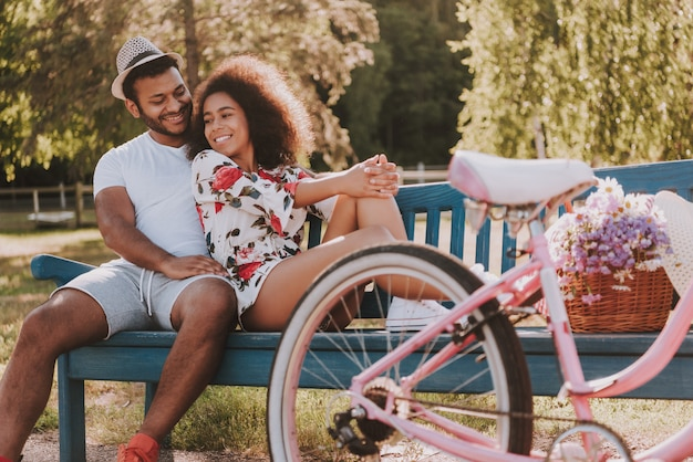 Couple sitting on bench in park bicycle date Premium Photo