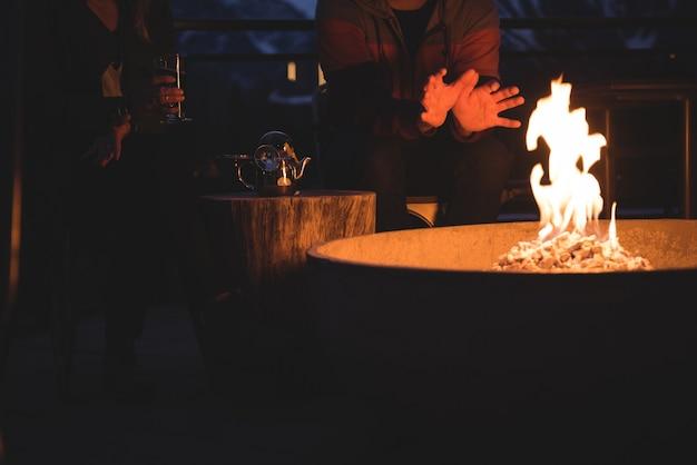 Coppia seduta da una buca per il fuoco Foto Gratuite