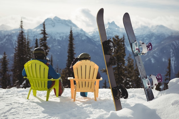 Couple sitting on chair by snowboards at snow covered mountain Free Photo