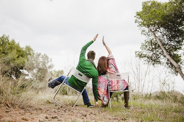 Couple sitting on chairs putting their hands together Premium Photo
