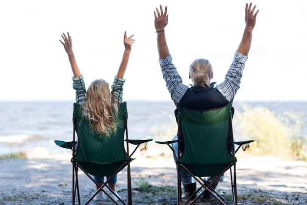 Coppia seduta su sedie con le mani in aria Foto Gratuite