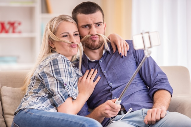 Couple sitting on the couch at home, using telephone. Premium Photo