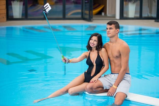 Couple sitting on edge of swimming pool Premium Photo