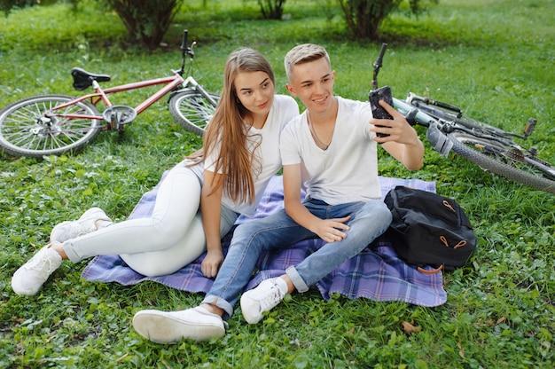 Пара, сидя в парке с велосипедом Бесплатные Фотографии