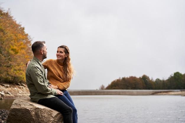 Пара сидит на берегу озера и смотрит друг на друга на открытом воздухе с озером Premium Фотографии