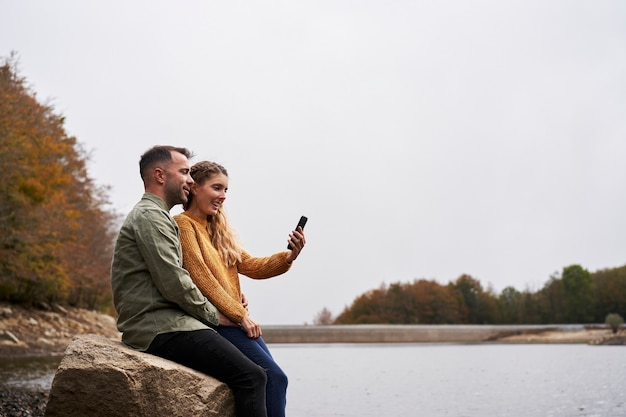 Пара сидит на берегу озера, делает селфи Premium Фотографии