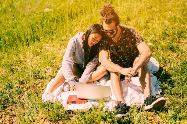 Couple sitting in meadow and looking into laptop Free Photo
