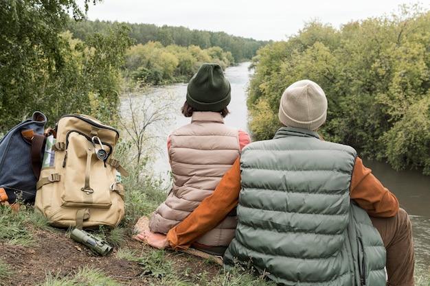 Пара сидит на земле, глядя на реку Бесплатные Фотографии